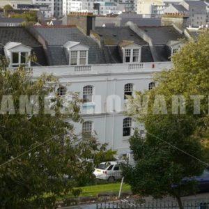 ENGLAND – CIRCA 2011: English apartments through trees - Actor Stock Footage