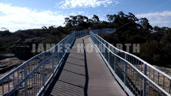 Pan up catwalk in forest. - Actor Stock Footage