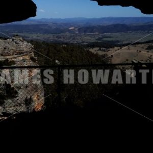 Walk into cave on a cliff to view on the other side. - Actor Stock Footage