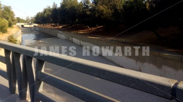 Walking by empty Los Angeles concrete water river channel. - Actor Stock Footage
