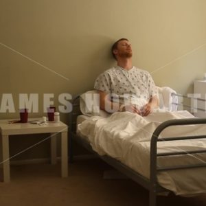 A male patient in hospital in bed. Wide shot. - Actor Stock Footage