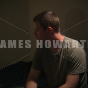 A man looks at pill bottle in his room. - Actor Stock Footage