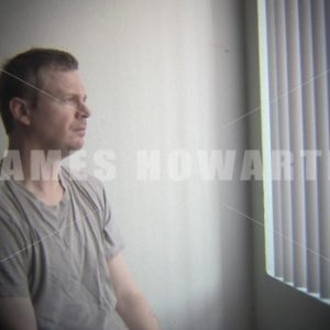 A man looks out the window in contemplation. - Actor Stock Footage