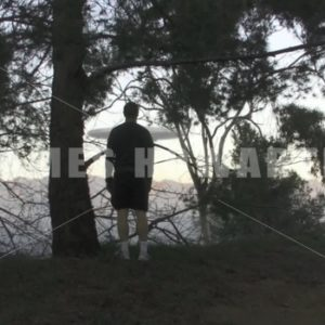 A man looks out to a UFO rising in the forest. - Actor Stock Footage