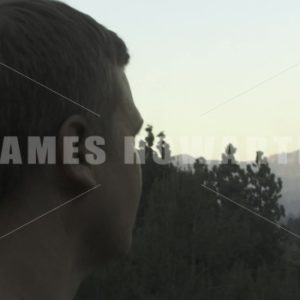 A man looks out to mountains. - Actor Stock Footage