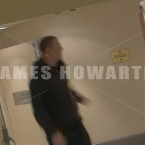 A man running down a hallway at a left angle and turns. - Actor Stock Footage