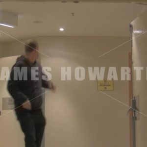 A man running through doorway hallway at low angle. - Actor Stock Footage