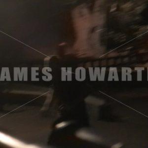 A man runs past playground at night. - Actor Stock Footage