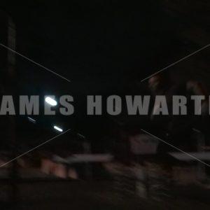 A man runs past playground park at night. - Actor Stock Footage