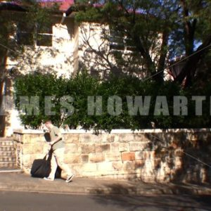 A man walks to a house with his bag. - Actor Stock Footage