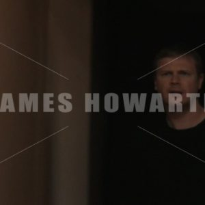 Close up of a man walking cautiously down a hallway. - Actor Stock Footage