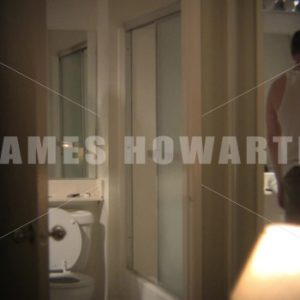 Man goes to have shower and hears door. - Actor Stock Footage